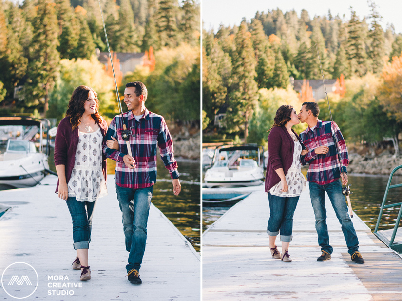 The couple walks down the docks sharing a beautiful kiss along the way in the engagement photo shot by the photographers of Mora Creative Studio