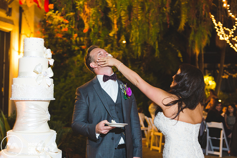 The stunning bride shoves a piece of cake into her husband's mouth after the cake has been cut as photographed by the photographers of Mora Creative Studio