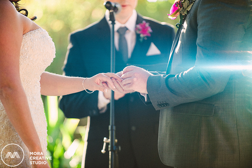 Our groom is placing his bride's ring on her finger as the beading of her dress sparkles and the groom's boutonniere is brightly shown in the photo at the LA River Center and Garden